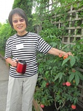 PHOTO BY DICK TRTEK - Helena Wagner shows visitors to her Clackamas garden an abutilon, a scarlet-hued Chinese plant that resembles an upside-down rose.