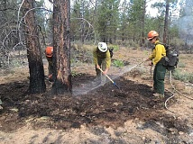 PHOTO COURTESY OF OREGON DEPARTMENT OF CORRECTIONS - Crews work to put out a hotspot on the Akawana Fire, in western Jefferson County, on Saturday. The fire, which was started by lightning on private land in the Lake Chinook Fire District on June 7, reached 2,094 acres by Saturday. The fire is now more than 80 percent contained.