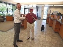 BARBARA SHERMAN - Inside the King City Columbia State Bank, branch manager Ryan Kliewer shakes hands with King City Lions Club member Bill Gerkin, who walked 'blind' for an hour when Kliewer offered to donate $60 to the Lions' Sight and Hearing Foundation; however, Gerkin's dog Chewie was ready to hit the road.