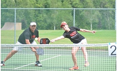 SPOKESMAN PHOTO: COREY BUCHANAN - A player lunges for the ball near the net during the Summer Sizzle pickleball tournament at Memorial Park.