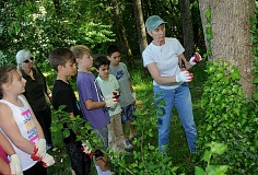 REVIEW PHOTO: VERN UYETAKE - Friends of Hallinan Heights Woods co-coordinator Barbara Fisher works with Hallinan students to remove ivy.