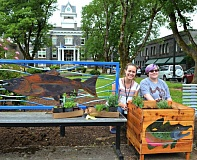PHOTO COURTESY OF THE CITY OF ST. HELENS - Mainstreet Program Coordinator Anya Mocha and St. Helens High School alumna Lindsey Smith sit by one of the completed planters placed near the Columbia County Courthouse Plaza in downtown St. Helens. Smith completed two planters with mirror images of spawning male salmon that frame a bench currently installed near the plaza.