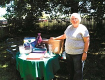 ANGELICA TRUE - Molalla Area Seniors treasurer and rummage sale coordinator Pat Torsen stands with a pile of items to be sold on July 16.