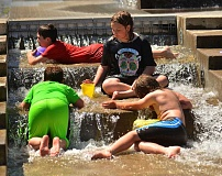 SPOKESMAN PHOTO: VERN UYETAKE - From left, Asher Beasley, Avery Beasley, Henry Harbottle and Theo Harbottle cool off in the water park at Murase Plaza June 21.