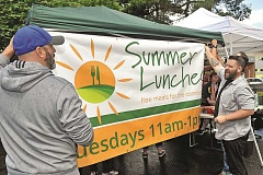 SPOKESMAN PHOTO: VERN UYETAKE - Brad Peterson, left, and Jake Schwein of Heart of the City put up a banner for the summer lunch program. The program is open to all community members.