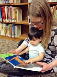 SUBMITTED PHOTO - A Lake Oswego mom reads to her daughter at the Lake Oswego Public Library.