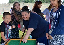 SPOKESMAN PHOTO: JAKE BARTMAN - Coffee Creek Correctional Facility inmate Kelly Patterson, center, plays a carnival game with her children (from left) Judah Dunam, Kiya Skerritt and Hailey Skerritt at the 15th annual Through a Childs Eyes event July 9.