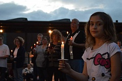 GAZETTE PHOTO: RAY PITZ - Kaydence Harris holds a candle during a candlelight vigil Wednesday night at Cannery Square Plaza
