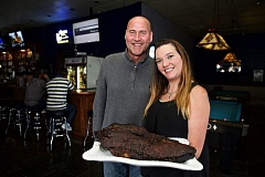 TIMES PHOTO: JAIME VALDEZ - Jerry Todd, general manager of Jo's Bar & Grill, and Brooke Auvil, a bartender at the bar, hold a brisket just out of the oven. Jo's will be participating, along with other barbecue restaurants, in a promotion for local nonprofits this summer.