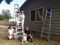 BARBARA SHERMAN - Carolyn Ackerman (on ladder), owner of Let Carolyn Paint It!, poses with new employee Kat Kress (left) with her rescue dog Stan, and business partner Lihau Kekahuna with Ackerman's rescue dog Bear.