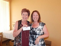 PMG PHOTO: BARBARA SHERMAN - At the Summerfield Clubhouse on July 14, Sandy Brewer (left), chairwoman of the Summerfield Women's Golf Club's charity fundraiser, holds a check for $8,000 made out to the Caring Closet that was gratefully accepted by Caring Closet Director Rose Money.
