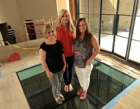 REVIEW PHOTO: VERN UYETAKE - Natalie Long (from left) Nancy Allen and Jamie Harris pose on the glass floor over the wine cellar at the luxury home they're building for the 2016 Street of Dreams in West Linn.