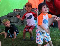 TIDINGS PHOTO: ANDREW KILSTROM - From left, Zack Campbell, Patrick Harris and Daxos Keavney enjoy the summer weather with a parachute game.