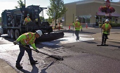 CONTRIBUTED PHOTO - Workers apply a slurry seal to Main Avenue, which will help extend the lifespan of the road.