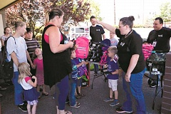 ANGELICA TRUE - TCC Verizon Wireless Backpack Giveaway event coordinator Jackie Winter (right) helps  families claim their free backpacks Saturday afternoon. Before the event even began, families were lined up waiting.