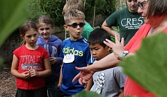 SPOKESMAN PHOTO: ANDREW KILSTROM - Campers intently listen to Robinwood Station member Nancy Muniz during a tour of the community garden. From left, Kiera Taylor, Lindy Kirsch, Aidan Sauer and Ethan Chan.