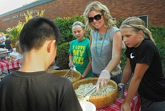 REVIEW FILE PHOTO: VERN UYETAKE - Jeniffer Pahl (center), with help from Reese Ericson (left) and Ella Peake, dishes up coleslaw at the Lakeridge Junior High School back-to-school barbecue last year.