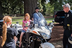 NEWS-TIMES PHOTO: CHASE ALLGOOD - Elisabeth Hansen sits on a Forest Grove Police motorcycle while her family takes photos.