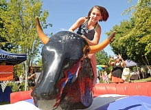 VERN UYETAKE - Candence Munson of Dundee shows her skill riding the mechanical bull.