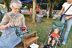 PHIS PASTERIS/TIGARD HISTORICAL ASSOCIATION - A modern-day child watches a 'grandma' use an old-fashioned apple-peeler at a previous Apple Harvest Festival at the John Tigard House in Tigard.