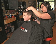 TIDINGS PHOTOS: VERN UYETAKE - Manager Kristy Booth works on a shorter haircut that has been the trend this summer.
