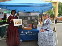 SUBMITTED PHOTO - McLoughlin Memorial Association volunteers Denyse McGriff (left) and Joan Williams don period costumes in staffing a booth at the First City Festival on July 23.