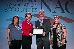SUBMITTED PHOTO - Clackamas County's A Safe Place Family Justice Center has been honored by the National Association of Counties (NACo) for its work to help victims of domestic violence. From left: Clackamas County Commissioner Martha Schrader,  NACo immediate past president Sallie Clark, Clackamas County Commissioner Paul Savas and Lt. Angela Brandenburg, director of A Safe Place.