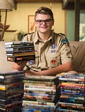 OUTLOOK PHOTO: JOSH KULLA - Max Lewis, 17, sits with a small portion of the DVDs he's received since he launched his donation drive three weeks ago. The effort is Max's project to earn the rank of Eagle Scout with the Boy Scouts of America.
