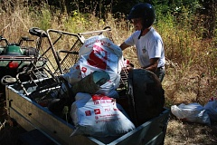 OUTLOOK PHOTO - Gary Klein loads trash and rusted shopping carts pulled from Johnson Creek into an ATV trailer.