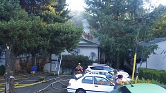 COURTESY PHOTO - Clackamas firefighters cut a ventilation hole in the roof of the burning apartment building.