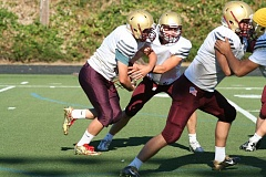 REVIEW PHOTO: JIM BESEDA - Milwaukie fullback Noah Ramirez takes a handoff from quarterback Jon Snyder as the Mustangs prepared for Friday's season opener against Benson.