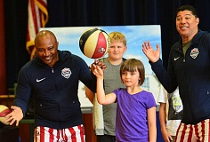 REVIEW PHOTO: VERN UYETAKE - Les 'Pee Wee' Harrison teaches third-grader Nuala Stenson a basketball trick.