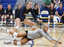 LON AUSTIN/CENTRAL OREGONIAN - Aspen Christiansen dives to play a ball during the Cowgirls victory over the Valley Catholic Valiants while Jennifer Roth covers. Christiansen finished the match with 38 digs.
