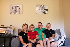 TIMES PHOTO: JAIME VALDEZ - Shawna and Dave Randall sit in the family room with their sons, Cade and Jace, below a picture at their home in Tigard. Shawna and Dave continue to raise money in memory of their youngest son, Cole Parker, who died when he was almost 11 weeks old from a genetic neuromuscular condition called spinal muscular atrophy.