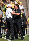 TRIBUNE PHOTO: JAIME VALDEZ - University of Oregon defensive coordinator Brady Hoke (right) gets a good-luck greeting from coach Mark Helfrich before the Ducks' opening game this year at Autzen Stadium.