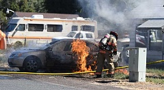 LON AUSTIN - Firefighters work to extinguish a car fire Monday that occurred at a residence on the corner of Combs Flat and Lincoln roads. The cause of the fire is still under investigation by the Crook County Sheriff's Office.