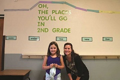 CONNER WILLIAMS - Second grader Gracie Fisher smiles for the camera with Rural Dell reading specialist Jessia Baumgartner. Fisher is among the top students for time read; she even fell asleep on one of her books from staying up late to read extra.