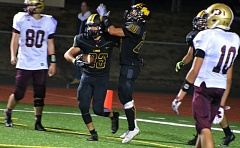 SPOTLIGHT PHOTO: JOHN BREWINGTON - Lions senior running backs Jax Ogle (33) and Haidon Allen (20) celebrate one of Ogle's two touchdowns against Milwaukie.