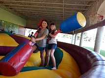 REVIEW PHOTO: CLIFF NEWELL - Good buddies Taya Uffert, left, and Alyssa Aebi, both 11 years old, take a break from biffing each other with padded poles for a friendly photo. Teen Lounge is structured to accommodate massive amounts of kids energy.