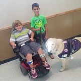 PHOTO COURTESY OF ANGELA DOESCHER - Stryder Doescher, with his service dog, Keebler, and his friend Landon Lockling, uses his new electronic wheelchair at school. Landon is Stryder's helper at Barnes Butte Elementary School, helping get him around, on elevators and through doors.