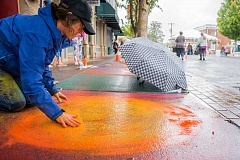 NEWS-TIMES PHOTO: CHASE ALLGOOD - Lori Hoyle embraces the rainy weather by incorporating the water into her chalk masterpiece. The umbrella to her left is one of many different that artists brought to shield their work.