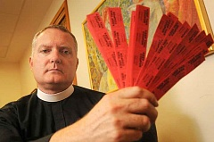 FILE PHOTO - The Rev. Jeremy Lucas of Christ Church Episcopal Parish in Lake Oswego holds the 150 tickets he purchased from a Gresham all-star softball team's raffle in July.