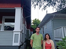 COURTESY: TONY SCHICK/OPB/EARTHFIX - Chris Palochak and Caitlin Poliak stand in between their home, right, and the home that has since been demolished. Their nine-month-old daughter's bedroom is only a few feet away from the demolition site and they're worried their daughter was exposed to lead dust that was released when walls coated in lead-based paint were demolished.
