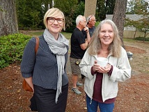 REVIEW PHOTO: CLIFF NEWELL - Carole Ockert (right) celebrates with a cup of tea as stone pillars are installed at the new Stafford Grove in First Addition. Joining her for the occasion was Sarah Selden, a senior city planner.