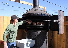 HOLLY SCHOLZ/CENTRAL OREGONIAN - Joe Litzinger, owner of Crossroads BBQ Pit and Pub, loads marinated chickens into the smoker, which is the restaurant's new main attraction. The restaurant now serves barbecue meats seven days a week at Third and Main.