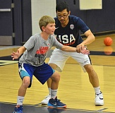 REVIEW PHOTO: VERN UYETAKE - Lake Oswego High Coach Marshall Cho helps Tyler Latta, 11, with his defensive stance at a basketball camp over the summer. Districts across the state are trying to find a way to incorporate more physical education time into their regular schedules during the school year.