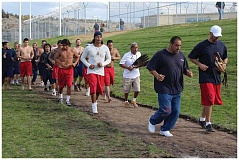 HOLLY M. GILL - Native American inmates who are veterans lead the final lap of the Native American Spirit Run at Deer Ridge Correctional Institution on Friday. Volunteer and organizer Owen Wallulatum, in white shirt holding a feathered staff, runs with the 30 or so inmates who participated in the day-long spiritual event, which was dedicated this year to the Standing Rock Tribe's protest of an oil pipeline that will run under their water source.