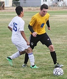 PHOTO COURTESY OF JEFF WILSON/MADRAS PIONEER - Cameran Jeppsen (9) plays the ball past Josh Rodriguez of the Madras White Buffalos. The White Buffalos won the match 7-1 to remain undefeated in Tri-Valley Conference play.