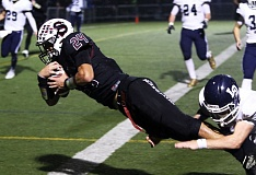 DAN BROOD - Sherwood High School senior David Morris, with Lake Oswego senior Adam Brumfield holding onto his legs, dives over the goal line to complete a 9-yard touchdown pass play.