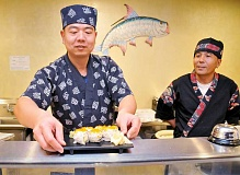 GARY ALLEN - Chef Li (left) serves up a fresh California roll under the tutelage of Chef Chen at Ichi Sushi in Newberg. The restaurant opened at the west end of downtown on September.